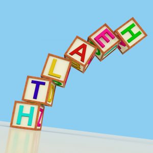 Wooden Blocks Spelling Health Falling Over As Symbol for Healthcare Or Failing Wellbeing